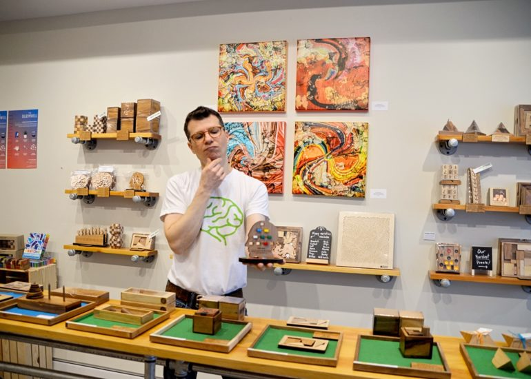 Man standing among various types of puzzles