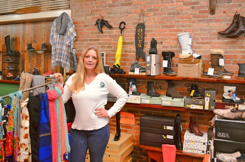 Cindy Brashear, owner of Cobblers Cottage, standing among the shop's winter boots collection.