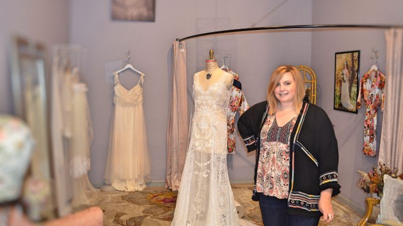 Geen June Bridal owner Layne Dann standing near bridal gowns