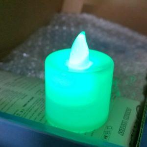 A tealight glows green